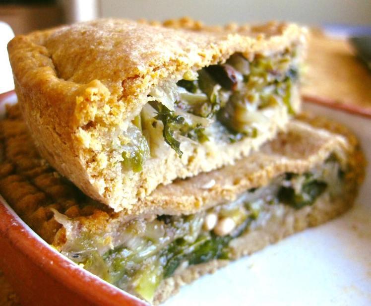 Torta salata con sfoglia semintegrale con scarola, uvetta, pinoli e olive nere al forno.